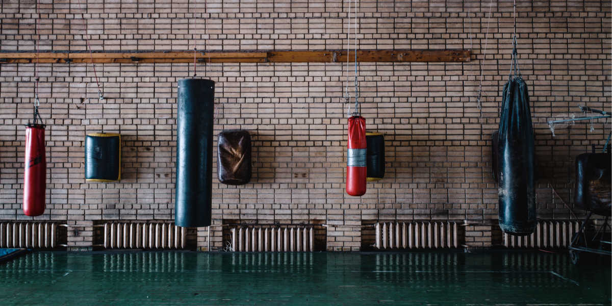 Gym with different types of punching bags on the wall